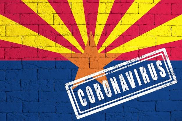 スタンプコロナウイルスで汚れたレンガの壁の背景に描かれたアリゾナ州の旗