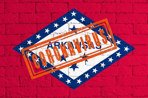 スタンプコロナウイルスで汚れたレンガの壁の背景に描かれたアーカンソー州の旗