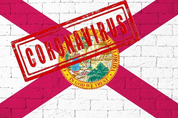 汚れたレンガの壁の背景に描かれたフロリダ州の旗。スタンプコロナウイルス、米国でのヘルスケア、エピデミック、病気のアイデアとコンセプト