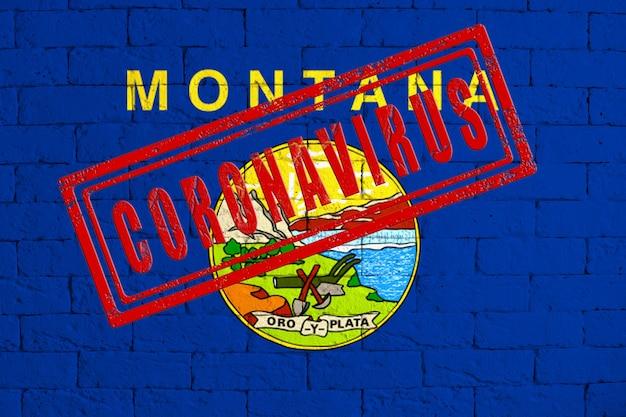 汚れたレンガの壁の背景に描かれたモンタナ州の旗。スタンプコロナウイルス、米国でのヘルスケア、エピデミック、病気のアイデアとコンセプト