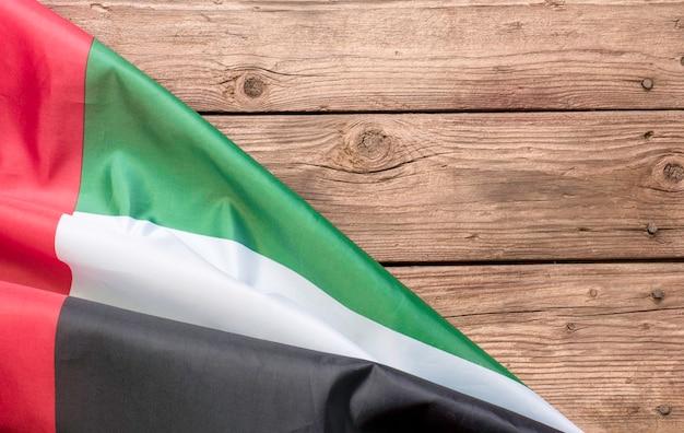 아랍에미리트의 국기와 어두운 나무 배경에 텍스트를 배치합니다.