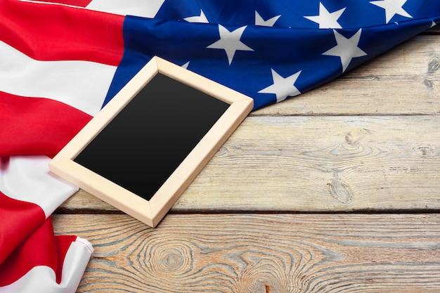 나무 배경에 아메리카 합중국의 국기. 재향 군인, 기념관, 독립 및 노동절의 미국 휴가.