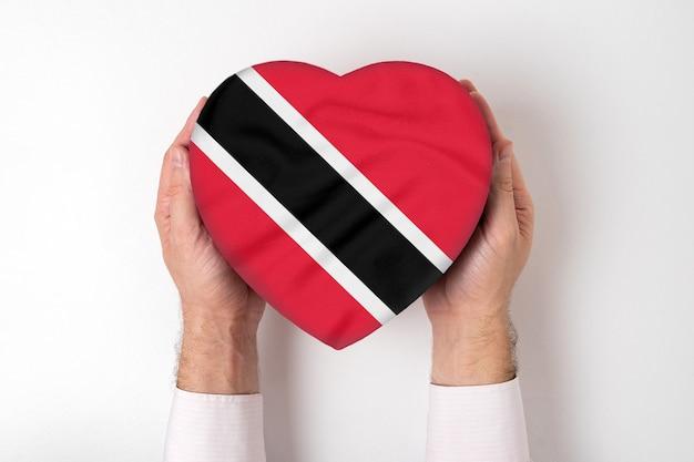 Флаг тринидада и тобаго на коробке в форме сердца в мужских руках. белый фон