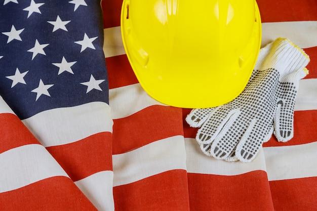 ハッピー労働者の日のアメリカ合衆国の旗は黄色のヘルメットと手袋に愛国心が強い記号
