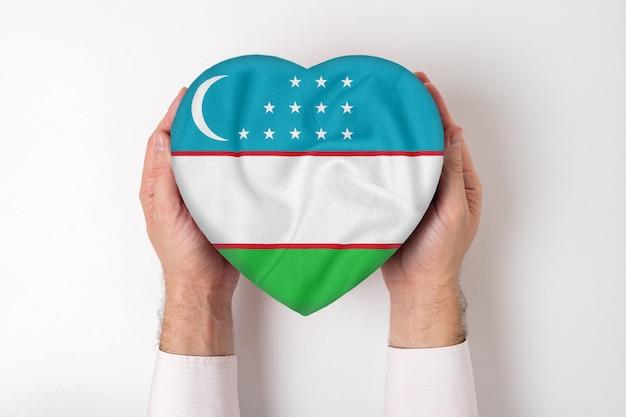 Флаг узбекистана на коробке в форме сердца в мужских руках.