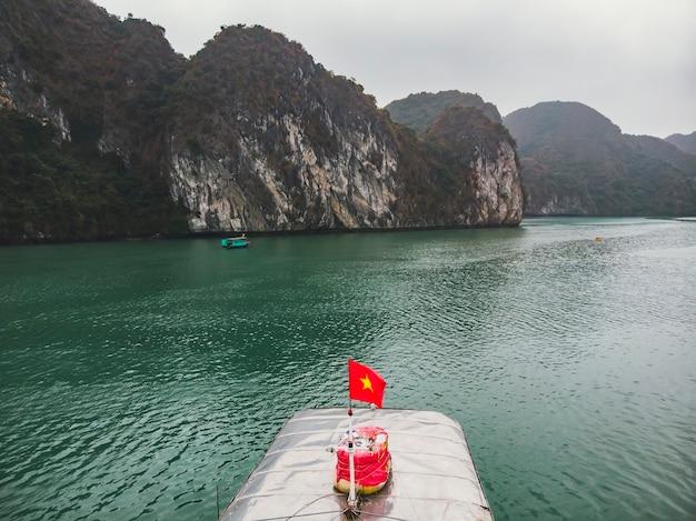 ベトナムの旗、金の星が付いた赤い旗、ベトナムの南シナ海のトンキン湾のハロン湾で船に羽ばたきます。カルストタワー-島と灰色の空が背景に表示されます。