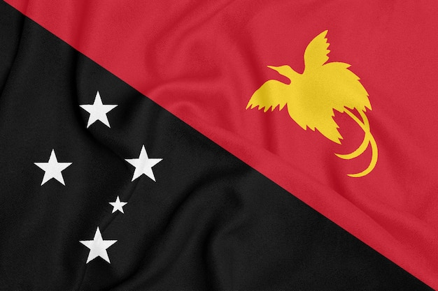 Flag of papua new guinea on textured fabric. patriotic symbol