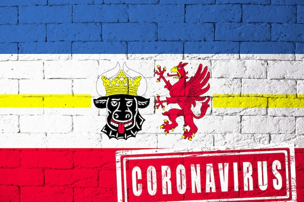 Flag of the regions of germany mecklenburg-vorpommern with original proportions. stamped of coronavirus. brick wall texture. corona virus concept. on the verge of a covid-19 or 2019-ncov pandemic.