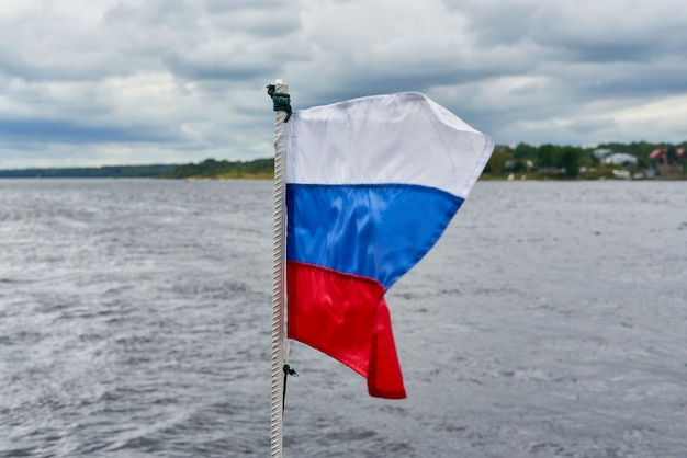 The flag of russia flies in the wind against the background of the seascape