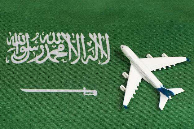 Flag of saudi arabia and model airplane. opening borders after quarantine. travels