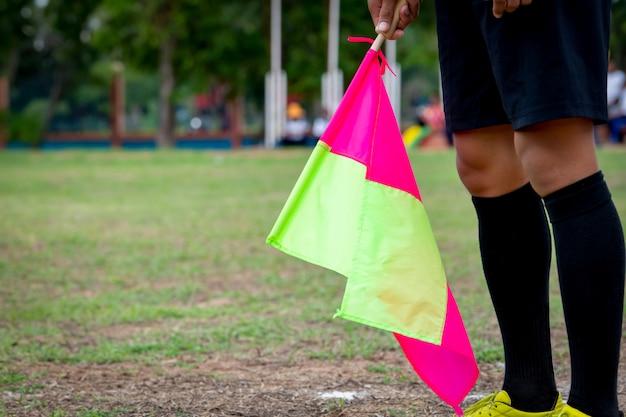 アシスタント審判サッカーの手にサッカーをフラグします。