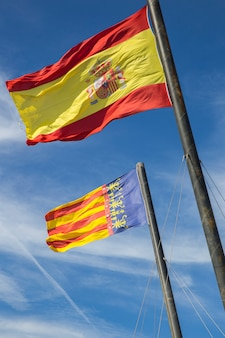 Flag of spain and the flag of valencia against the blue sky