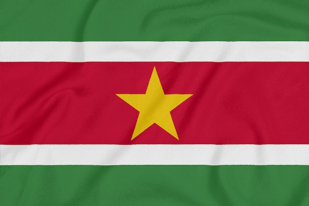 Flag of suriname on textured fabric. patriotic symbol