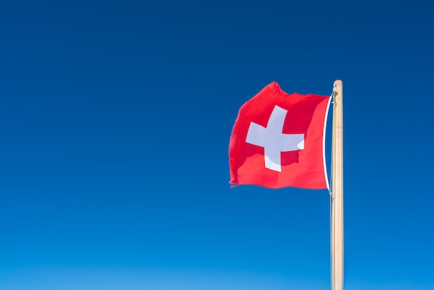 Flag of switzerland against the background of the blue sky.