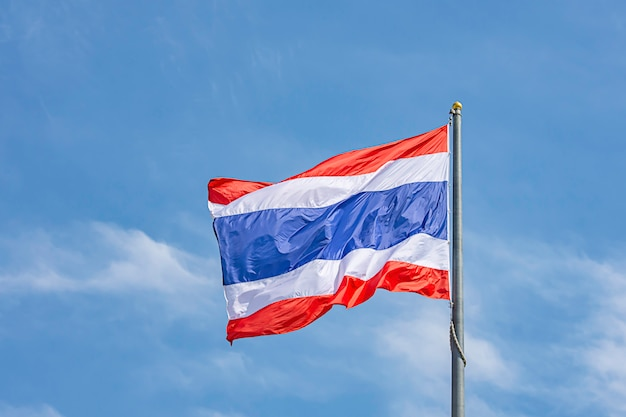 Flag of thailand on the pole and bright blue sky.