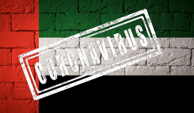 Flag of the uae or united arab emirates with original proportions. stamped of coronavirus. brick wall texture. corona virus concept. on the verge of a covid-19 or 2019-ncov pandemic.