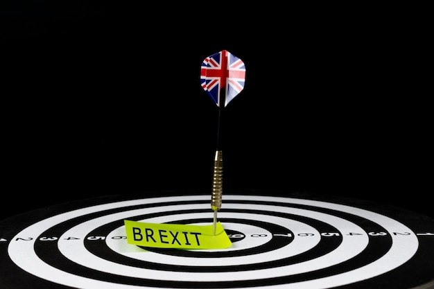 Flag of uk dart arrow hitting in the target center of dart board with text