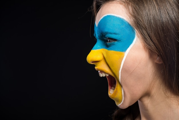 Flag of ukraine painted on the face woman.