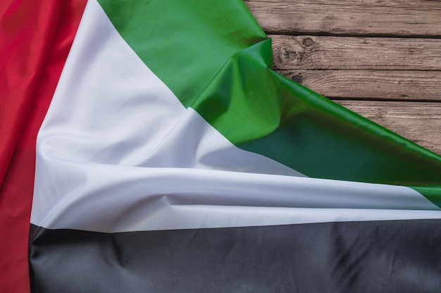 The flag of the united arab emirates lies on a brown wooden background with space for text or image
