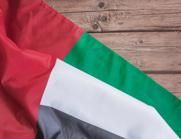 Flag of the united arab emirates and place for text on a dark wooden background.