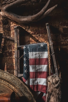 Flag of the united states hung on a metal stand in an ancient attic