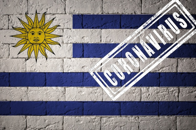 Flag of the uruguay with original proportions. stamped of coronavirus. brick wall texture. corona virus concept. on the verge of a covid-19 or 2019-ncov pandemic.