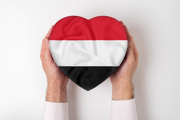 Flag of yemen on a heart shaped box in a male hands.