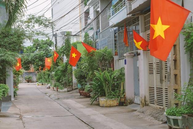 하노이의 작은 거리를 따라 깃발. 주택에 설치된 베트남 국기는 좁은 주거 차선입니다. 베트남 국경일을 기념하는 시민들의 애국심