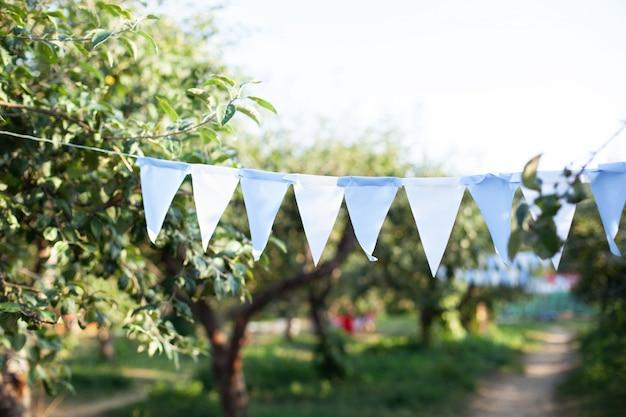 Флаги день рождения украшения висит на ветке дерева в саду. красочные флаги овсянки вися в парке. оформление вечеринки в саду.