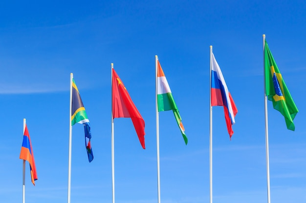 Flags of brics countries against blue sky