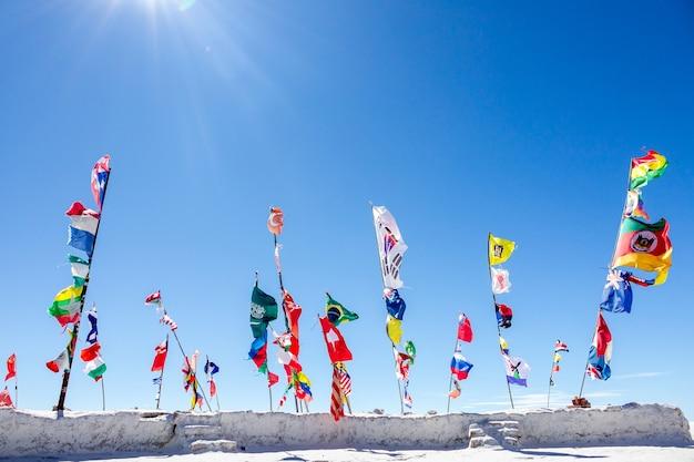 Flags countries landmark on salt marshes of uyuni