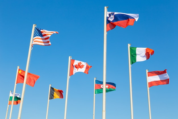 Flags of different countries fluttering agains blue sky