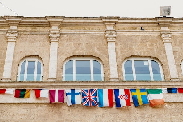 Flags of european countries hanging from a balcony in the italian city of matera.