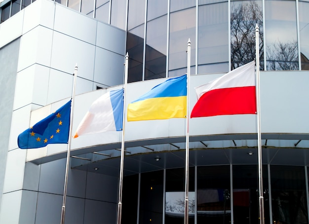 The flags of the european union, ukraine, poland, and other on office business building background