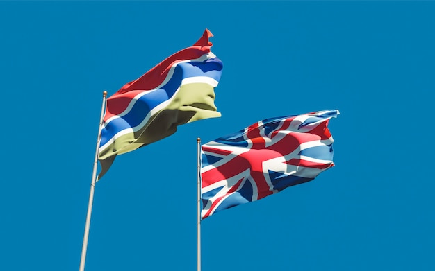 Flags of gambia and uk british on blue sky. 3d artwork