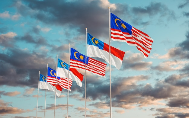 Flags of malaysian state malacca and malaysia waving together in the sky