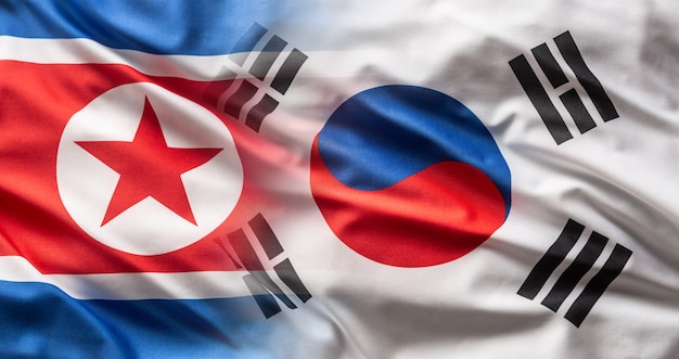 Flags of north and south korea blowing in the wind.