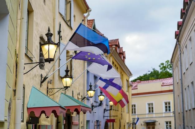 タリン市の中世の通りにあるエストニアとヨーロッパ諸国の旗。