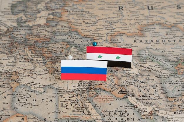 世界地図上のロシアとシリアの旗。概念的な写真、政治、世界秩序