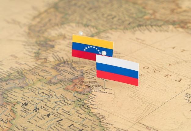 世界地図上のロシアとベネズエラの旗。概念的な写真、政治、世界秩序