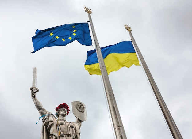 Флаги европейского союза и украины на фоне монументального памятника «родина-мать», посвященного великой отечественной войне в киеве, украина.