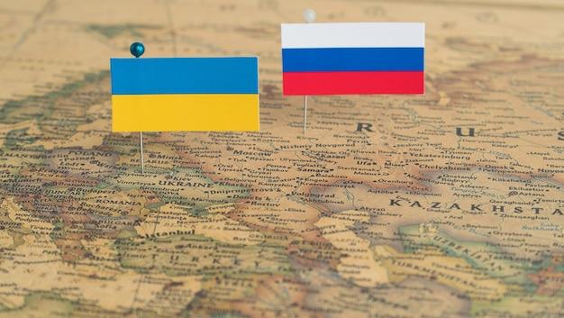 世界地図上のロシアとウクライナの旗概念的な写真の政治と世界秩序