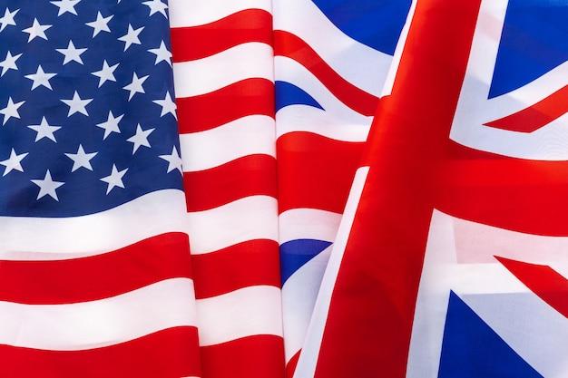 アメリカとイギリスのユニオンジャックの旗が一緒に手を振る