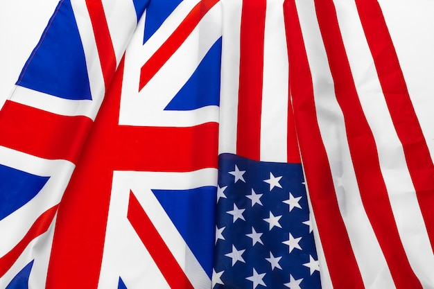 アメリカとイギリスのユニオンジャックの旗が一緒に手を振っています。