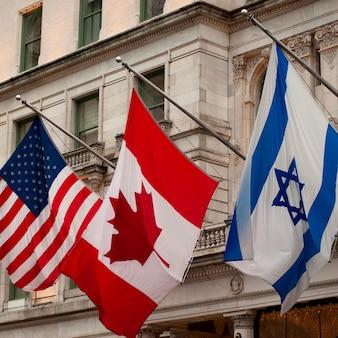 Флаги о здании в манхэттене, нью-йорк, сша
