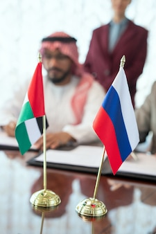 Flags of russian federation and united arab emirates on table against delegates reading and signing contract after negotiating at meeting