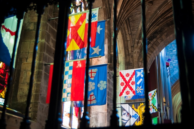 Flags of several scottish and english clans hung inside a scottish church in edinburgh.