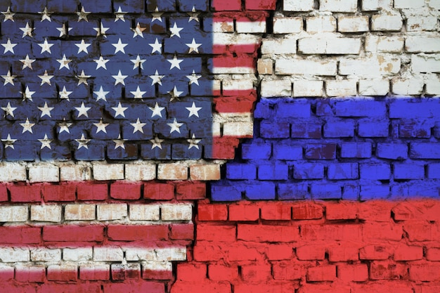Flags of united states of america and russia on the brick wall with big crack in the middle