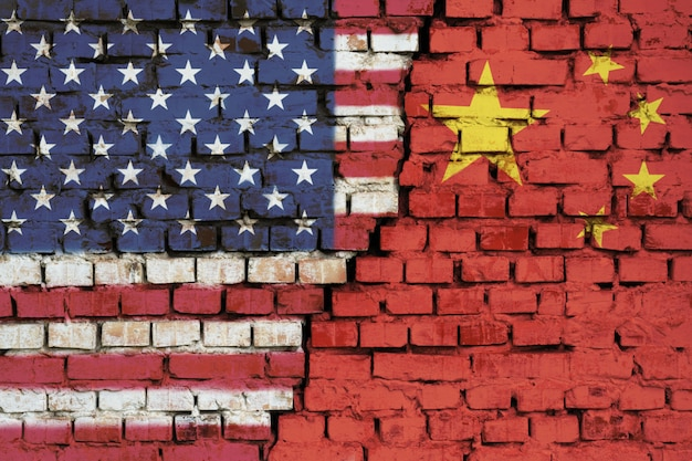 Flags of united states and china on the brick wall with big crack in the middle