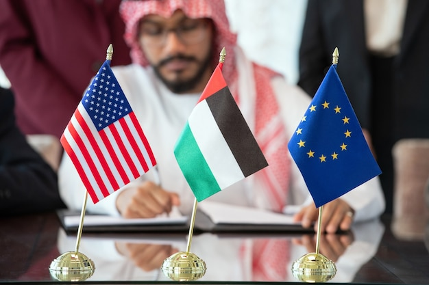 Flags of united states, european union and united arab emirates on table against delegate signing contract after negotiating at meeting